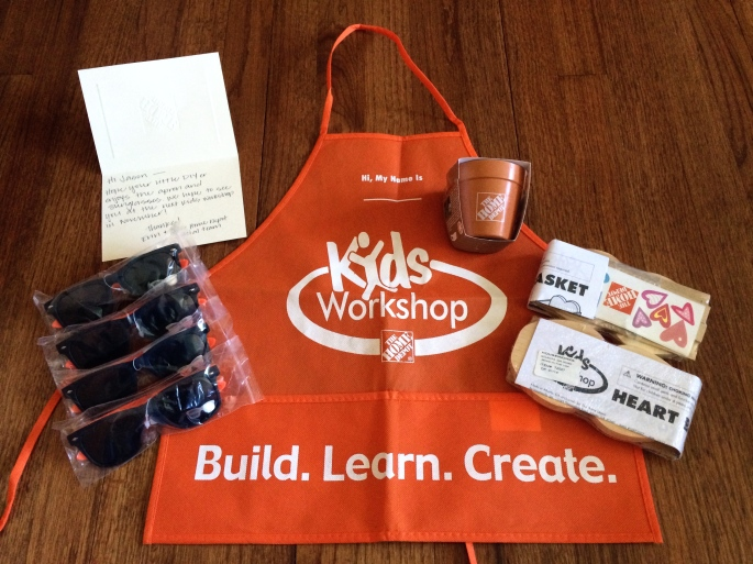 A kids apron, sunglasses, some DIY projects, and a handwritten note for Derek from The Home Depot Social Team.